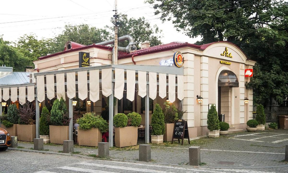 terasa restaurantului El Pato, acoperita cu copertina, imprejmuita cu ghiveci de flori