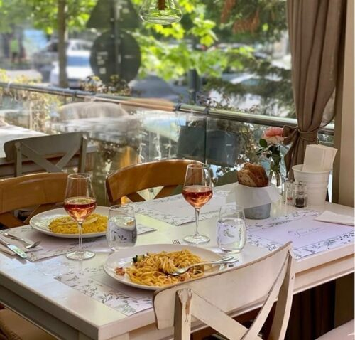 Prim plan cu o masa cu doua farfurii de mancare si doua pahare de vin de la restaurant Fior di Latte, una din terase deschise la 1 iunie