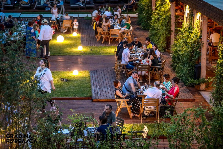 Gradina Floreasca din Bucuresti, cu mese ocupate de clienti si decor cu plante verzi