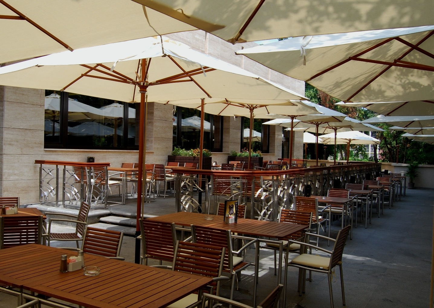 Terasa Hard Rock Cafe din Bucuresti cu mese din lemn si umbrele