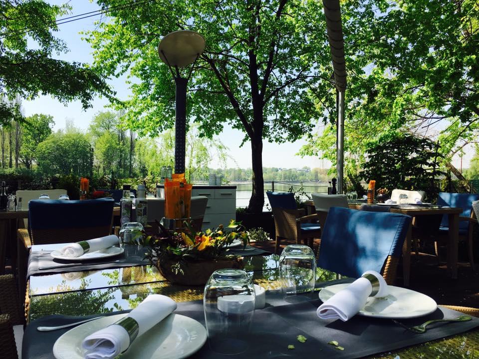 terasa restaurantului Isoletta, amplasata pe malul lacului herastrau, cu mese aranjate cu farfurii si pahare, una din terase deschise la 1 iunie