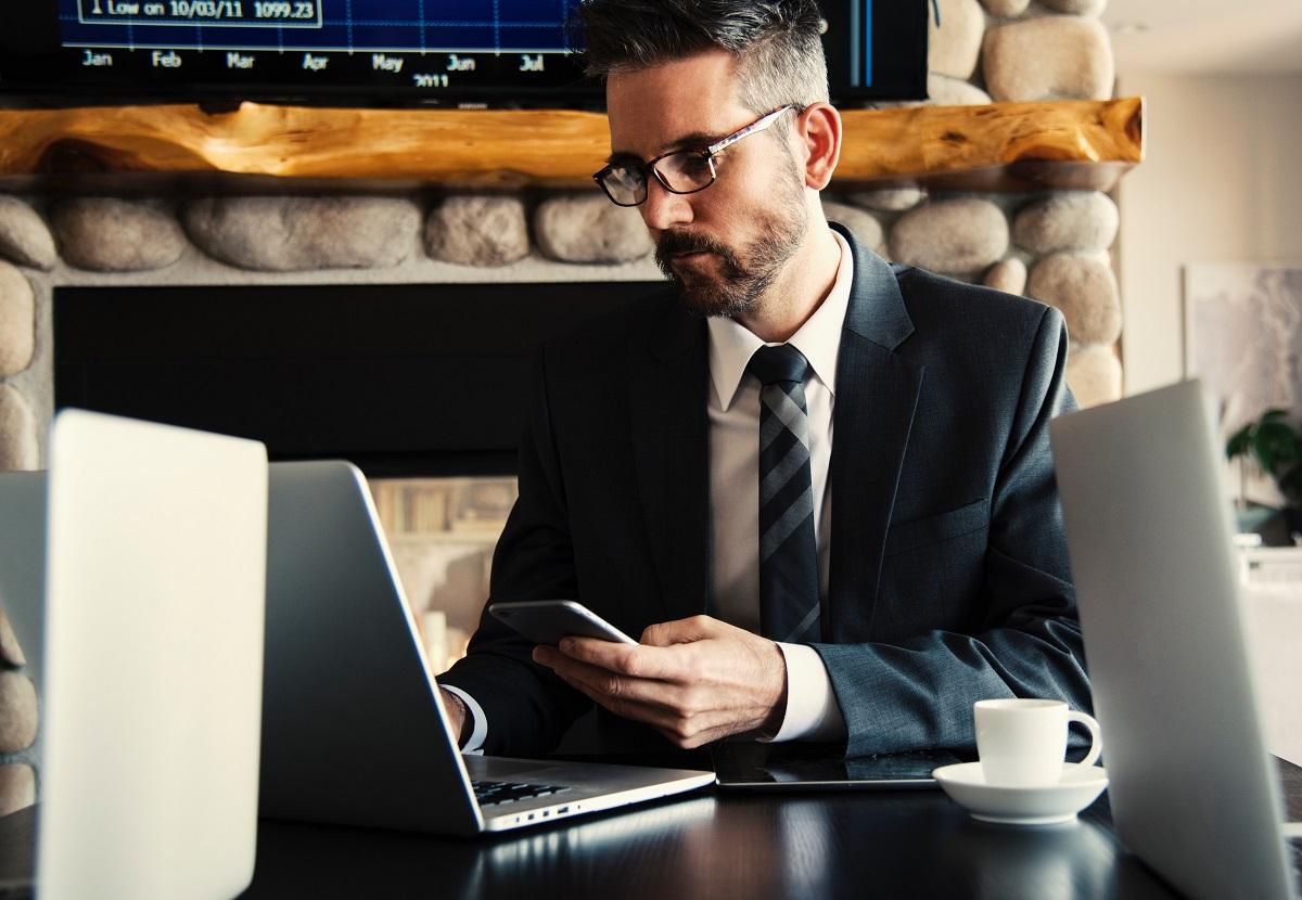 barbat de afaceri in costum negru, cu telefonul in mana, imagine pentru atitudinea de business în contextul COVID-19