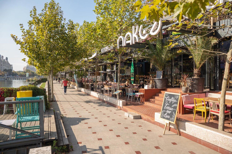 terasa naked kitch & beach bar by bordello, situata pe malul Dambovitei, inconjurata de copaci verzi