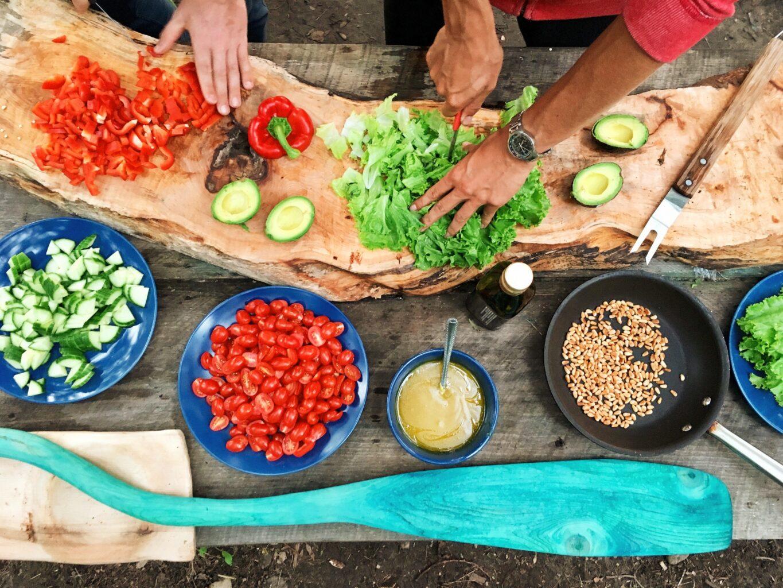doua maini care taie cu cutitul legume si boluri de diverse marimi cu legume, ca parte din o nutriție sănătoasă