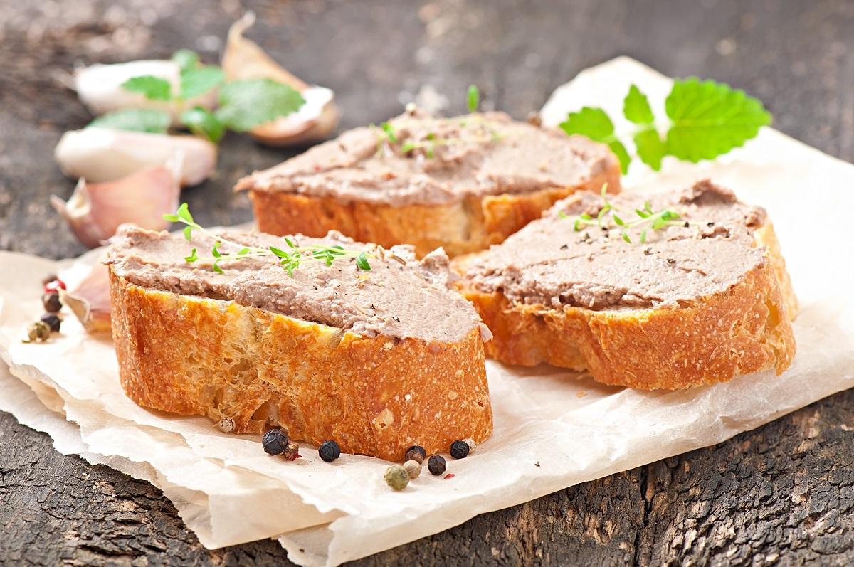 3 felii de paine unse cu pate de ficat făcut de casă, cu verdeata peste, asezate pe un propop crem