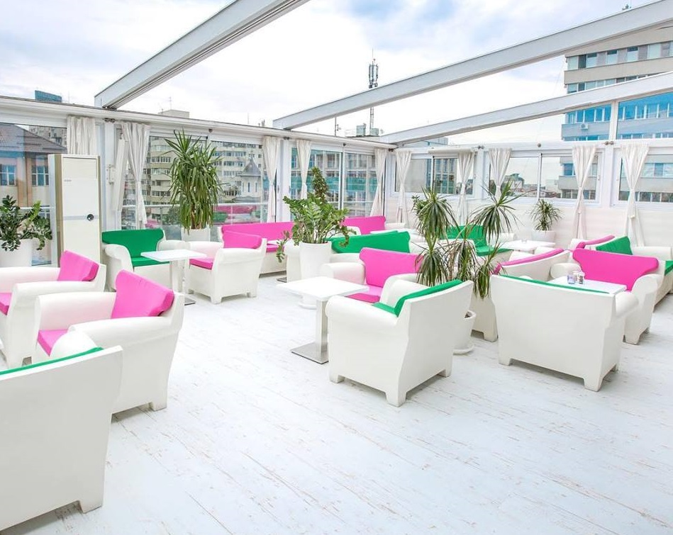 trasa Sky Bar din Dorobanti, cu podea alba, mese si scaune albe, cu perne roz, si pergola alba
