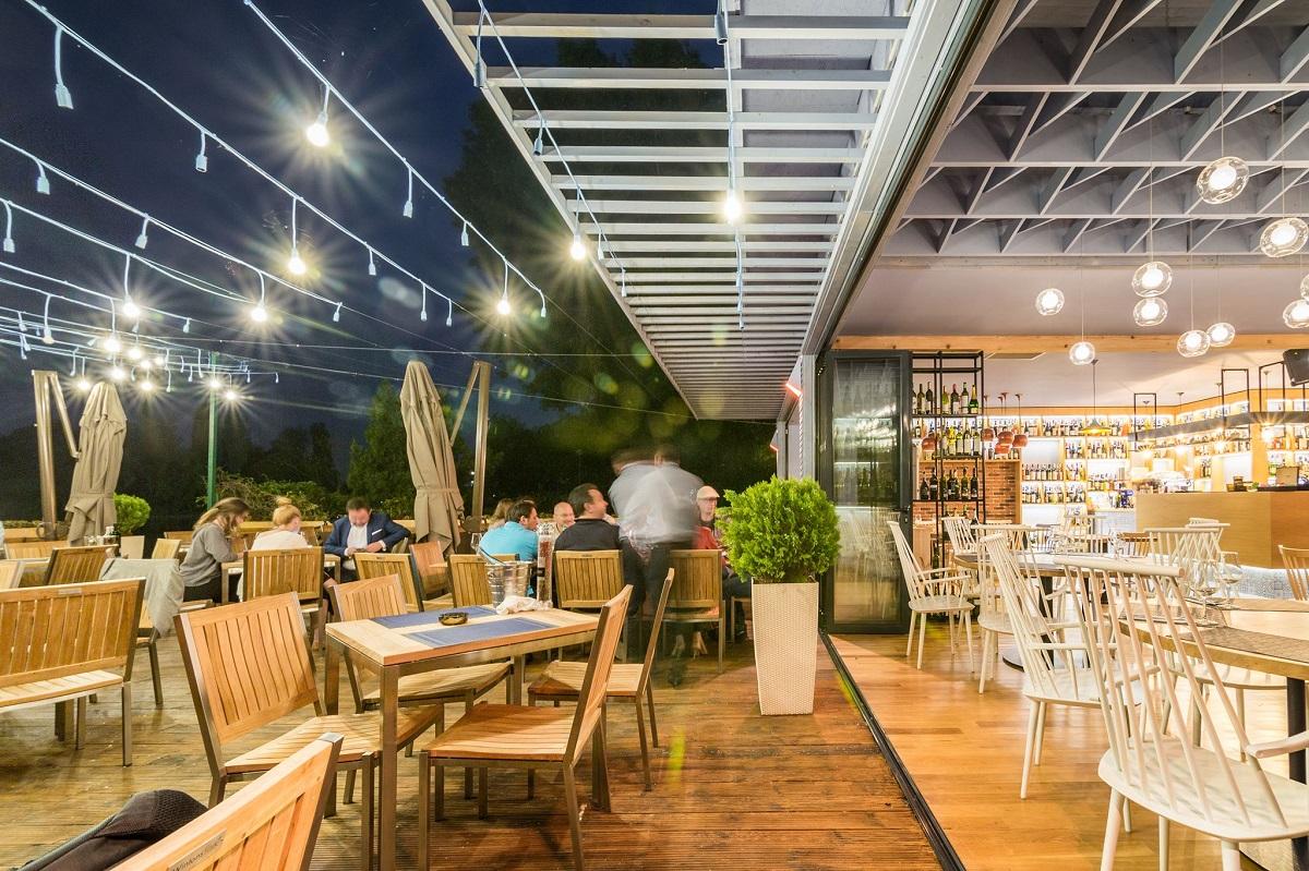 noaptea la tearasa Il Locale, cu mese si scaune din lemn si beculete aprinse, una din terase deschise la 1 iunie