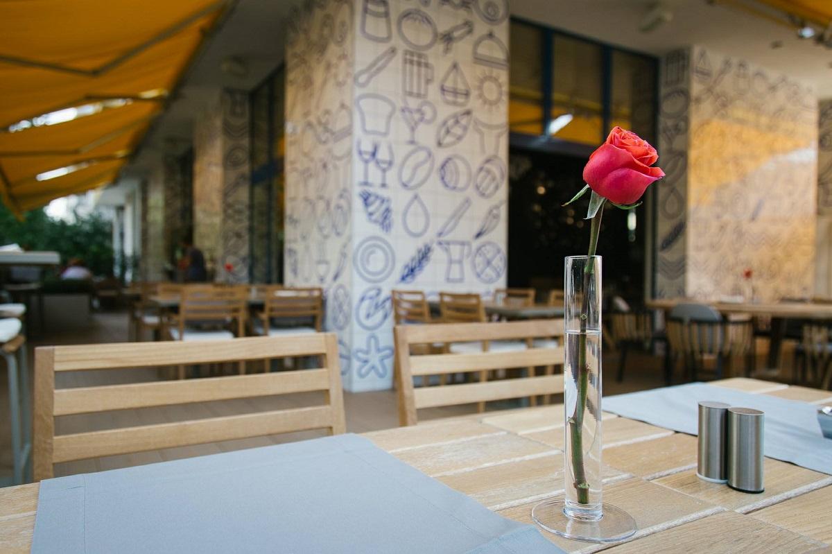 prim plan cu o masa de lemn cu scaune de lemn si o vaza cu trandafir de la sardin