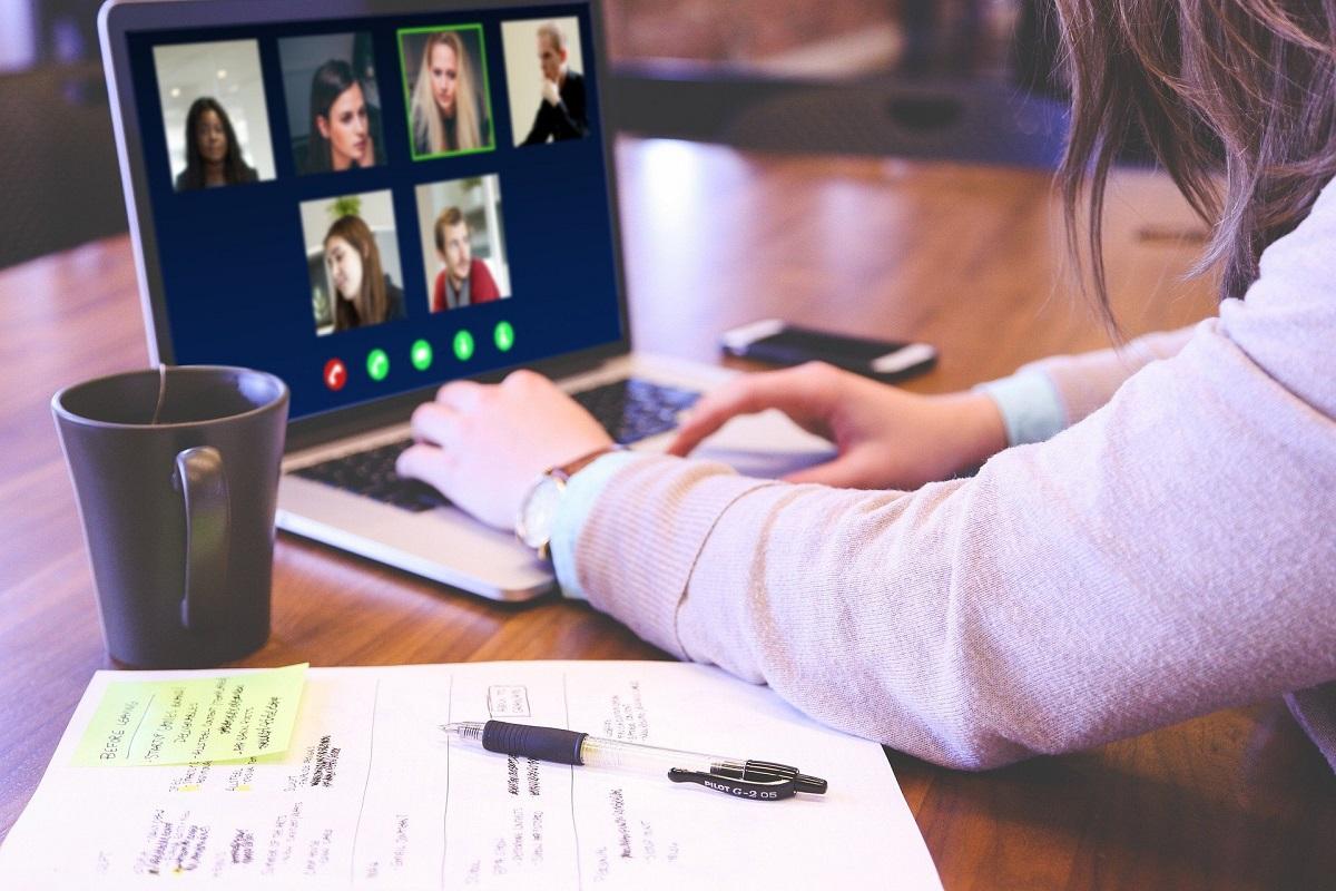 close-up cu mainile unei femei care lucreaza la laptop, cu un pix si caiet langa, imagine reprezentativa pentru de ce nu particip la webinarii