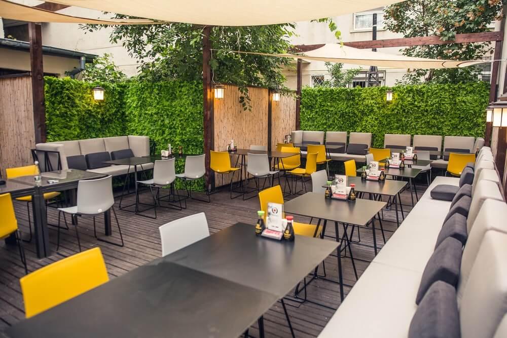 terasa Zen Sushi Dorobanți, cu mese metalice, scaune albe si galbene si canapele din stofa
