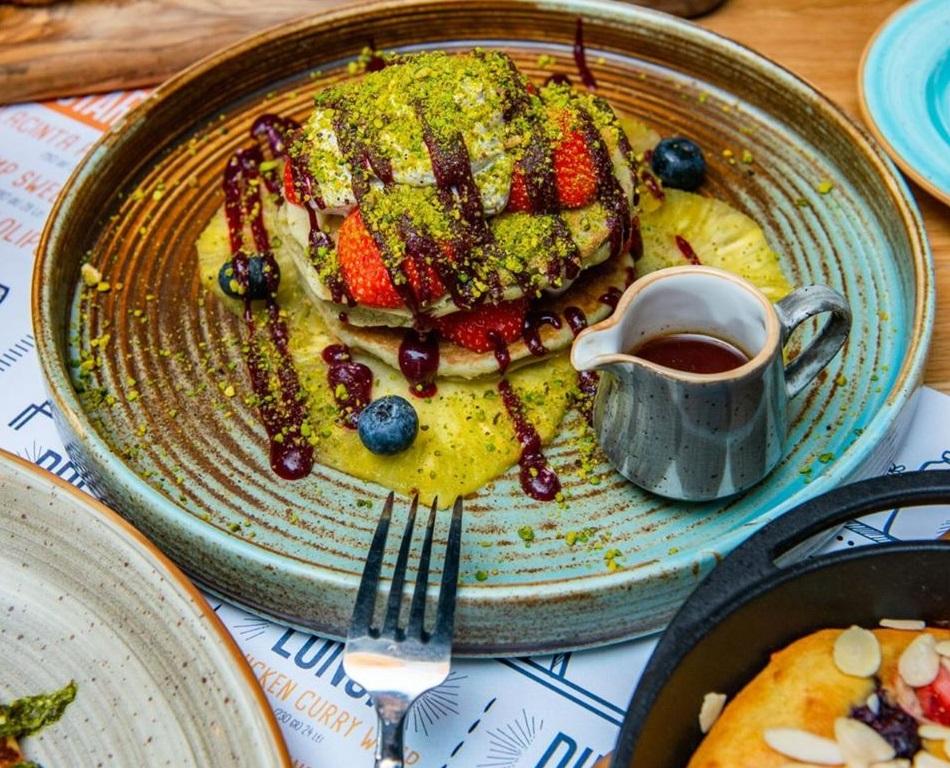 o portie de matcha pancakes cu clatite, frisca, ceai matcha si fructe de padure de la Pio Bistro, pentru micul dejun pe terasă