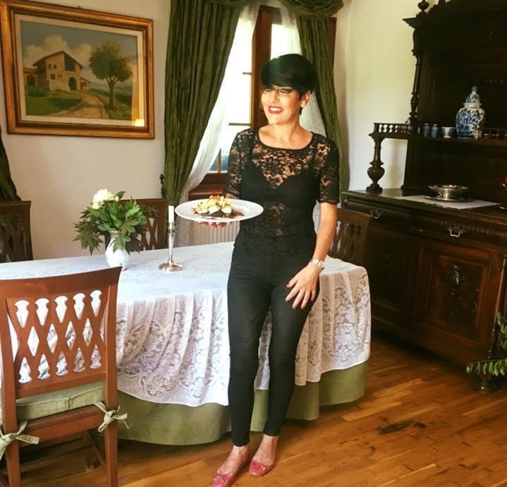 Patrizia Paglieri, imbracata in negru, servind o farfurie de mancare