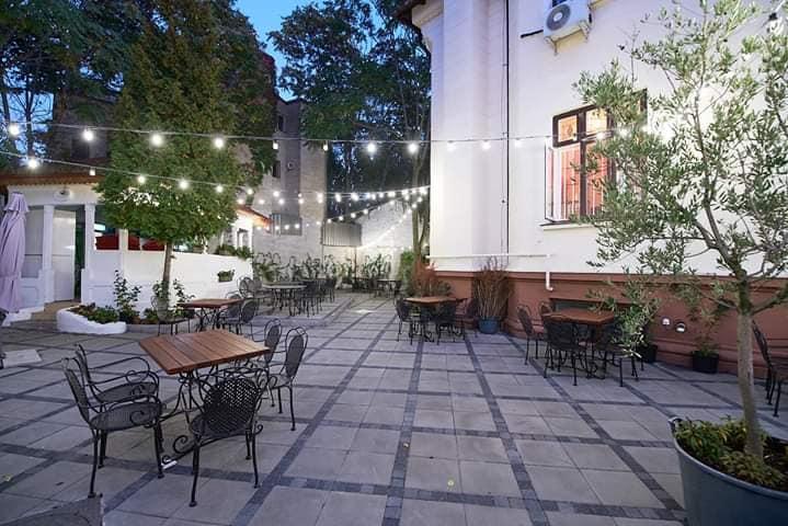terasa restaurantului Cia Niki, in curtea unei case memoriale, cu mese distantate, si luminite suspendate, apirnse