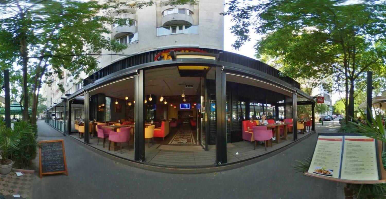 imagine panoramica cu terasa retina by traffic, la parterul unui bloc, cu mese si scaune colorate