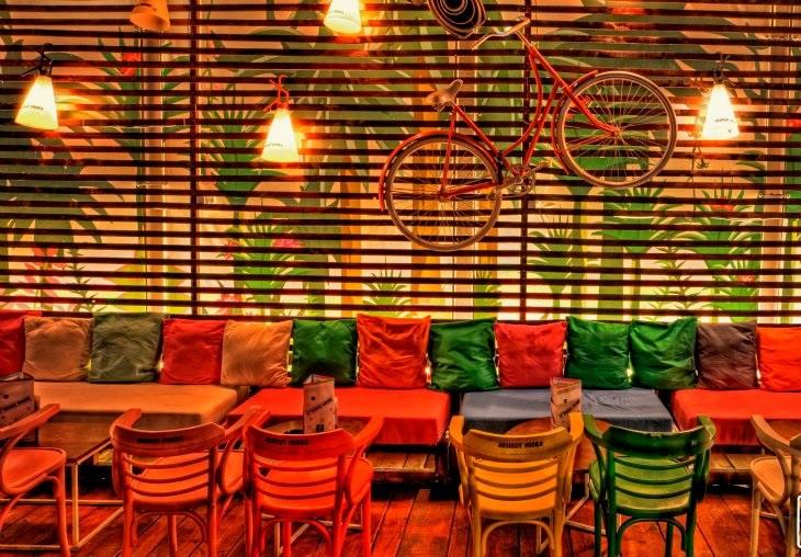 Terasa Storage Room cu mese, scaune si canapele colorate, si un panou de lemn in spate pe care sta atarnata o bicicleta
