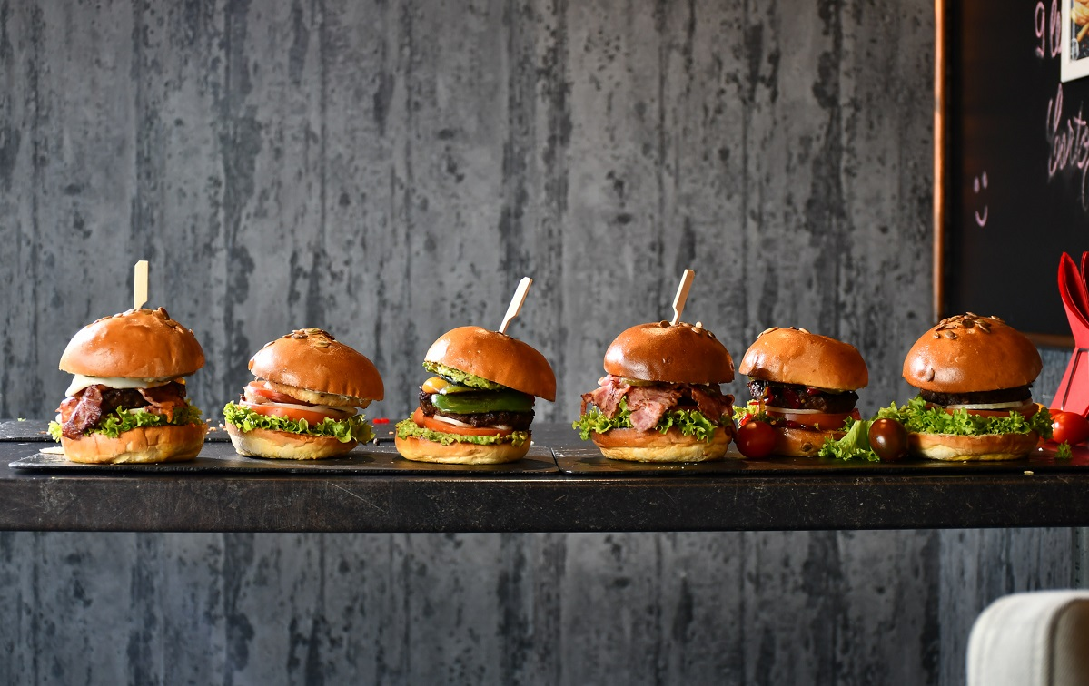 burgeri asezati in linie, pe o masa, pe fundal gri, burergi de la zvetto burger
