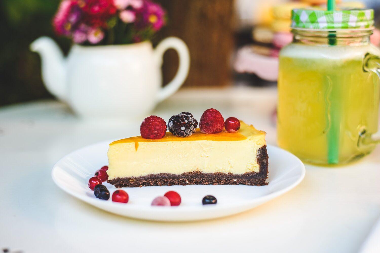 felie de cheesecake pozata lateral, cu fructe de padure deasupra si pe langa, in farfurie, si vaza cu flori in fundal