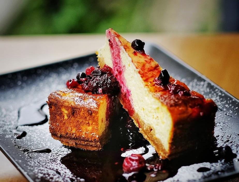 doua felii de cheesecake suprapuse, cu sos de fructe de padure, pe o farfurie neagra, la restaurant Pow Wow