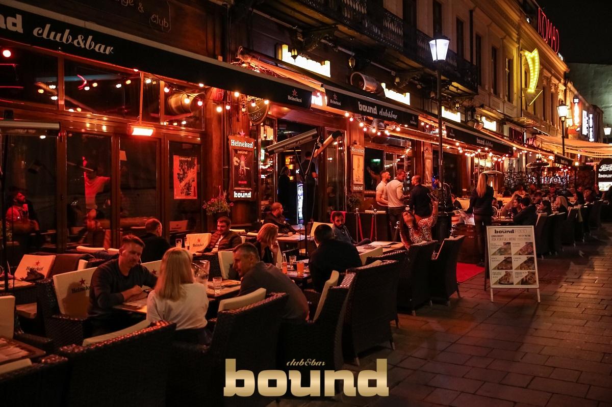 sir de mese cu clienti in fata la club bound, pe terasa, fotografiata noaptea