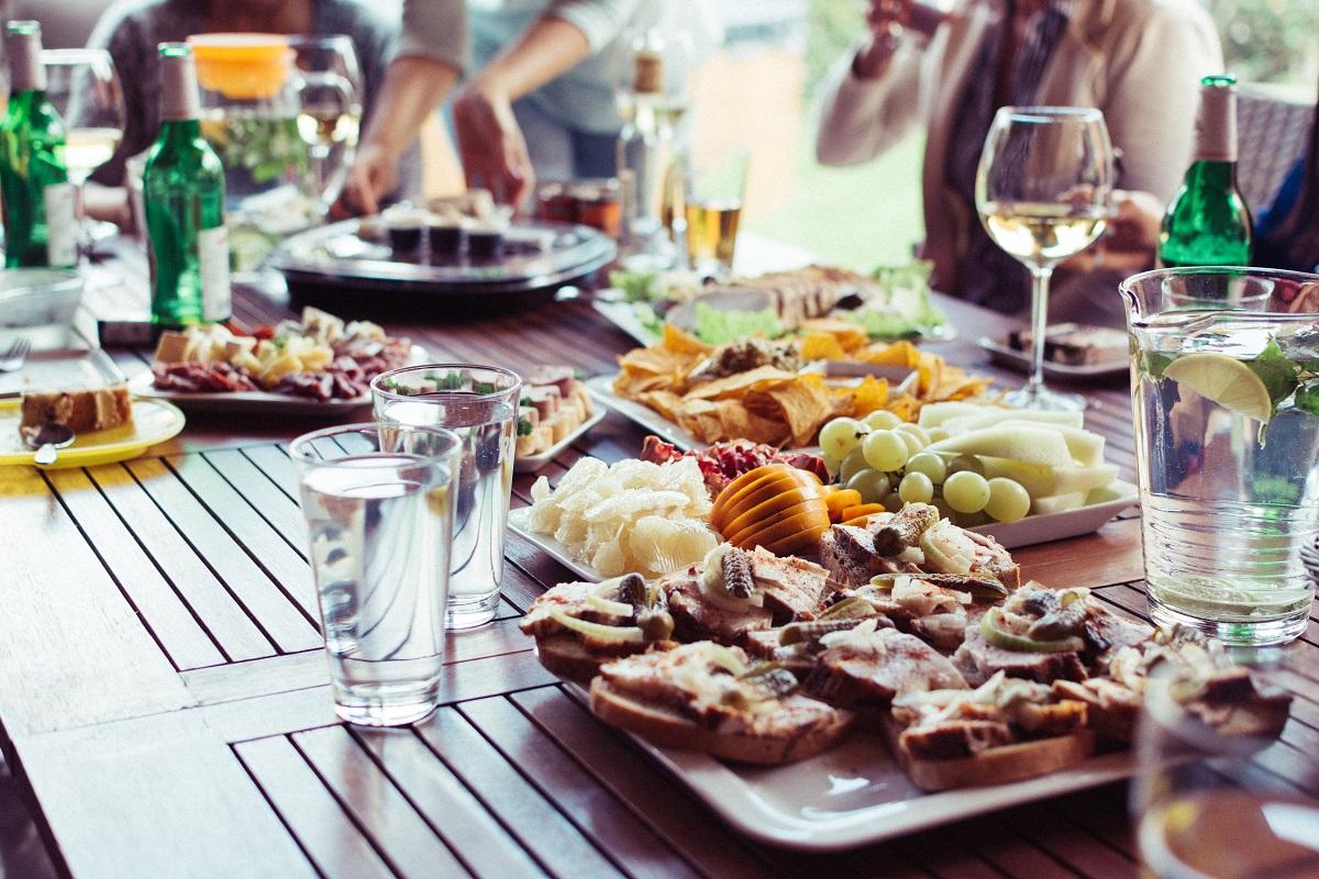 masă plina cu farfurii de mancare si pahare de apa si vin, imagine sugestiva pentru combinații de alimente
