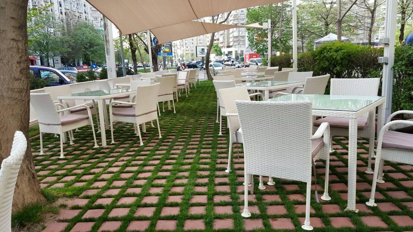 Terasa restaurantului El Bacha, cu mese si sacune albe, pe pavaj cu iarba