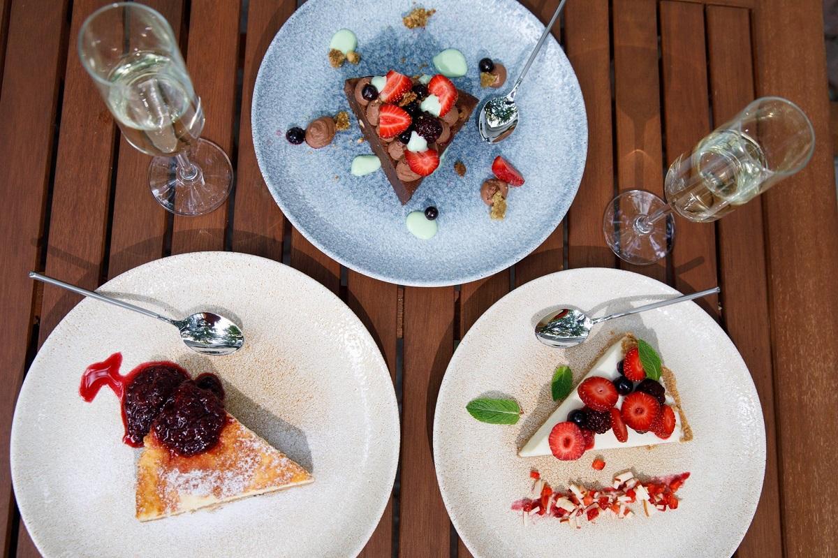 3 farfurii cu 3 felii de prajituri, dintre care una cheesecake si alta cu cacao, toate ornate cu fructe de padure, fotografiate de sus, la restaurant Suento din București