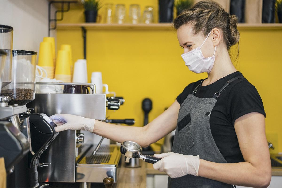 femeie cu masca si sort, preparand cafea la un espressor, imagine reprezentativa pentru masuri de siguranță la terasă