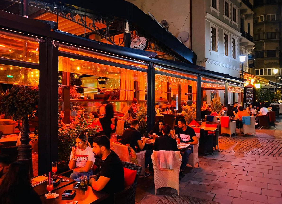 Terasa de la Freddo Bar and Lounge, fotografiata noaptea, cu mese amplasate in fata localului