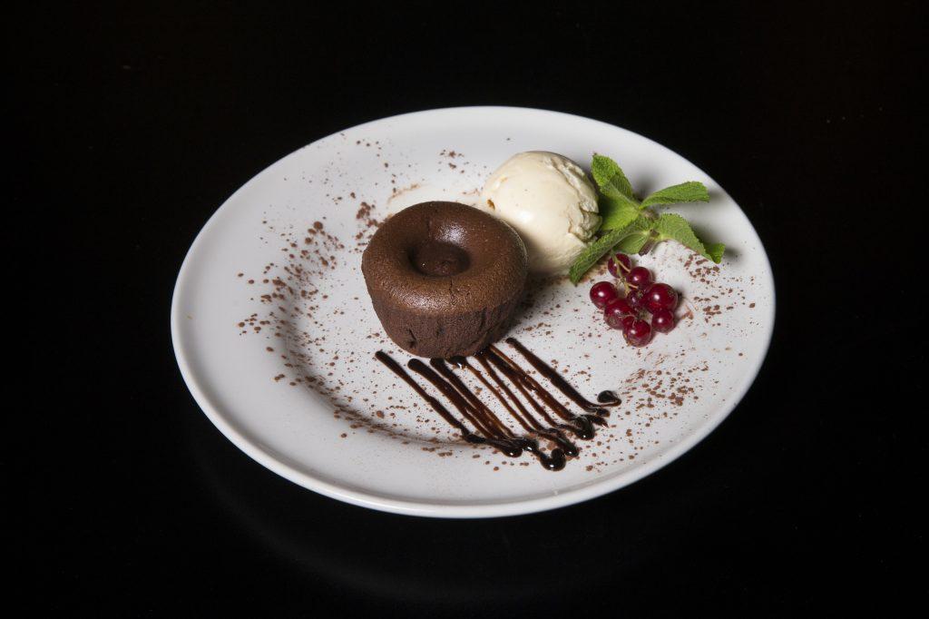 farfurie așba pe fundal negru, cu o prajitura lava cake si o cupa de inghetata de vanilie la restaurant il calcio by mr. val din bucurești