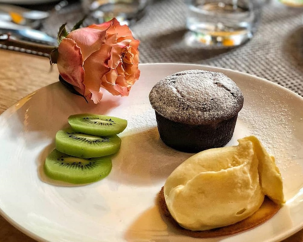 lava cake de la Sardin, cu inghetata de vanilie, felii de kiwi si un trandafir langa farfurie