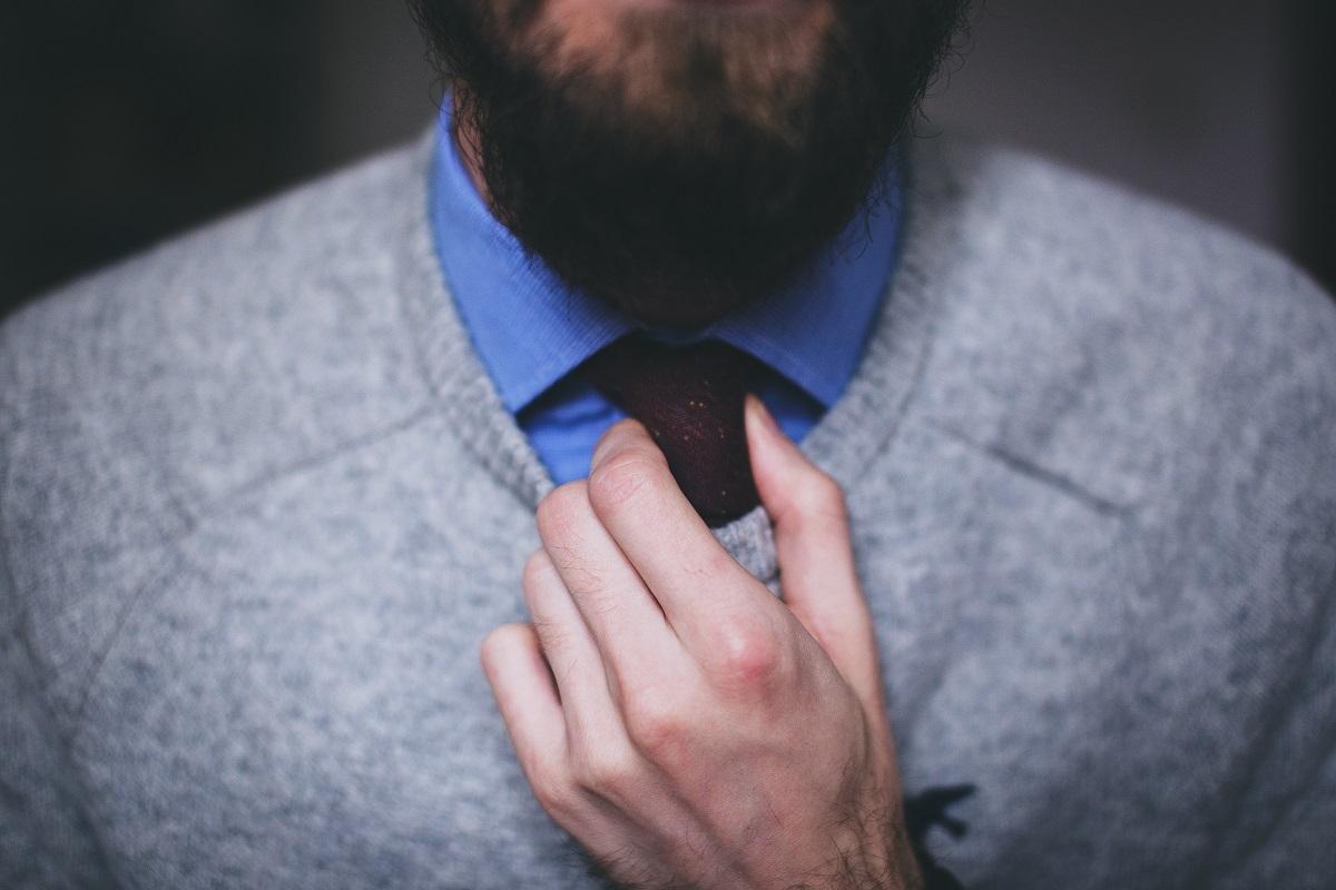 barbat cu pulover si cravata, imagine sugestiva pentru postura de lider