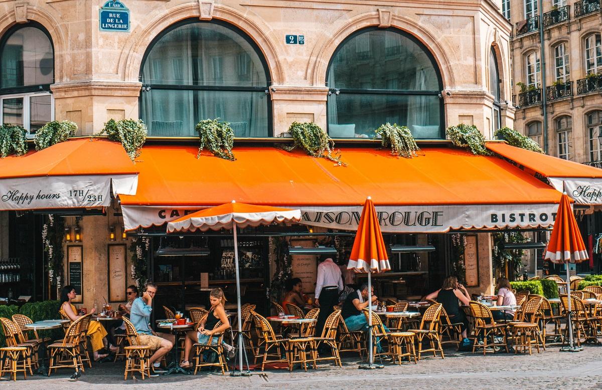 oameni stand la masa la o cafenea de strada cu copertina portocalie