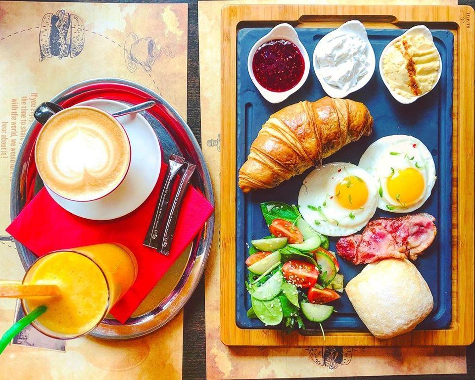 tava cu salata, bacon, oua ochiuri, croissant, dulceata si o farfurie cu cafea si fresh langa, la cafeneaua Les Bourgeois