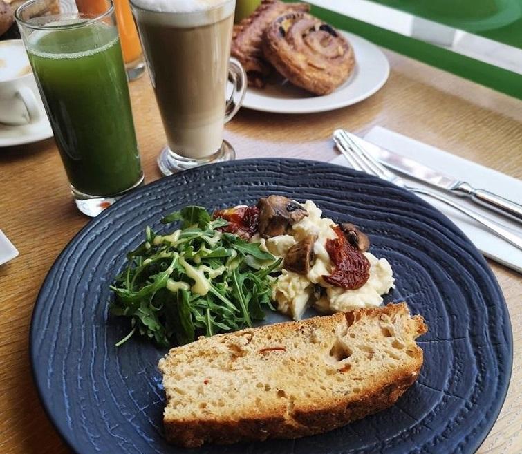 farfurie albastra cu o felie de paine prajita, omleta si salata verde la micul dejun pe terasa la caffe citta