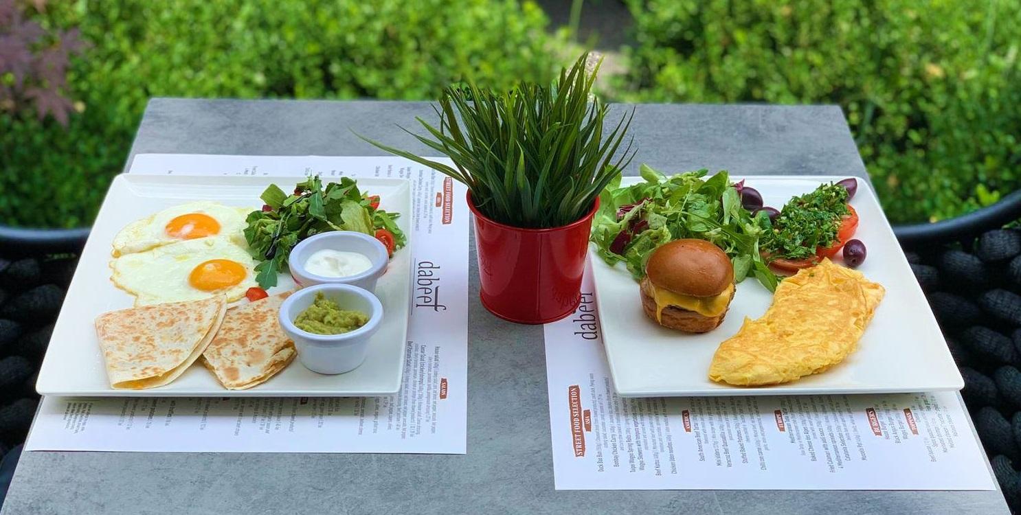 masa pentru 2 persoane cu omleta si burger intr-o farfurie, si oua ochiuri cu salata in alta, si un ghiveci mic cu plante in mijloc, pentru micul dejun pe terasă la dabeef