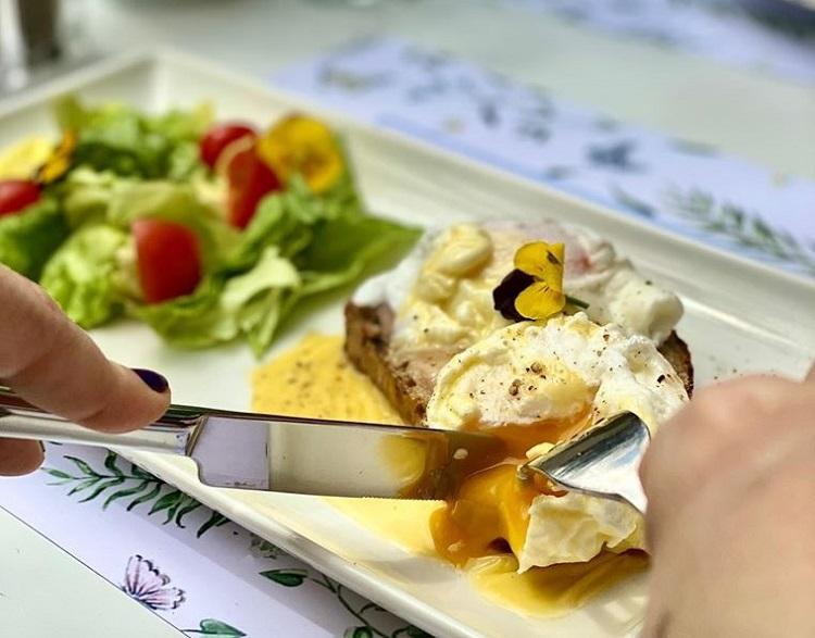 prim plan cu o persoana care taie cu cutitul oua benedict asezate pe o farfurie langa salata de avocado, la micul dejun pe terasă