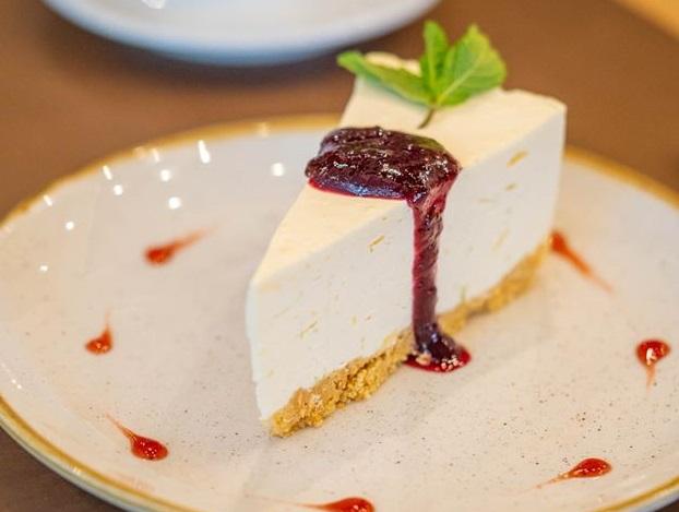 felie de cheesecake pe o farfurie alba, cu o frunza de menta si sos de fructe de padure, la restaurant daimon trattoria