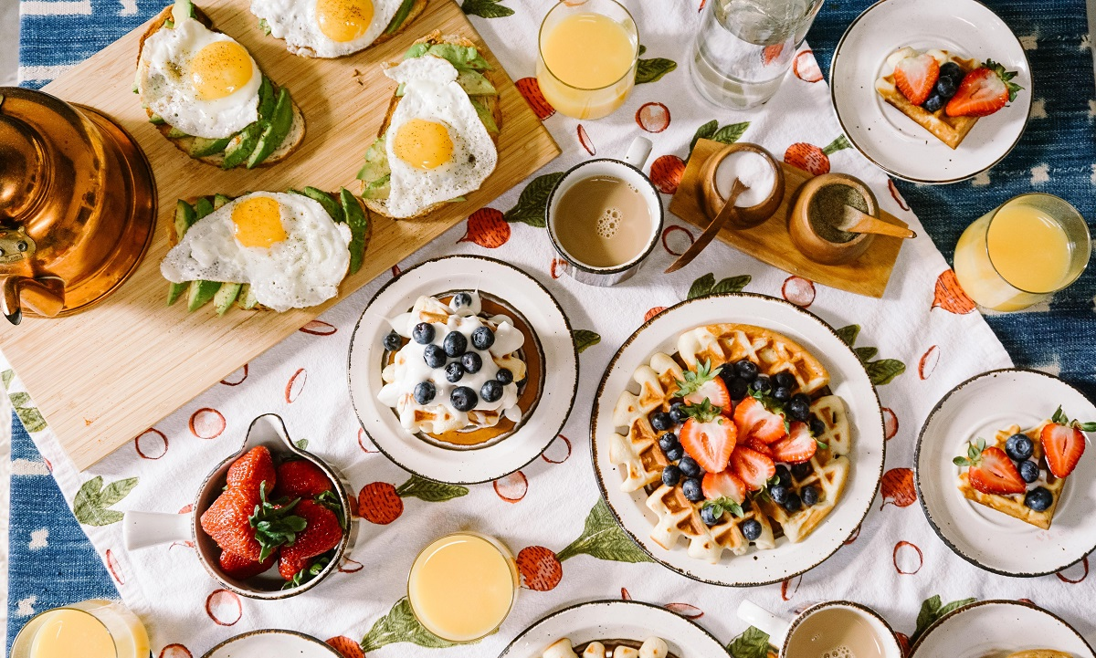 masa fotografiata de sus cu mancare pentru micul dejun pe terasa, cu oua ochiuri, vafe, iaurt cu afine, pahare cu fresh si cafea