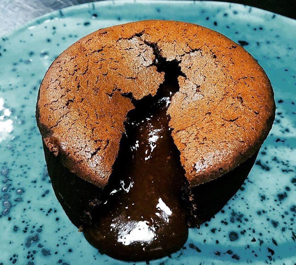 lava cake la studio 80 din bucurești, cu crusta crocanta si ciocolata care se revarsa din interior, asezata pe o farfurie albastra