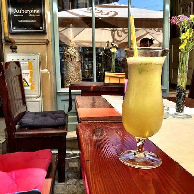 prim plan cu un pahar de smoothie galben cu pai, pe teras[ la Aubergine Healthy Food din Centrul Vechi