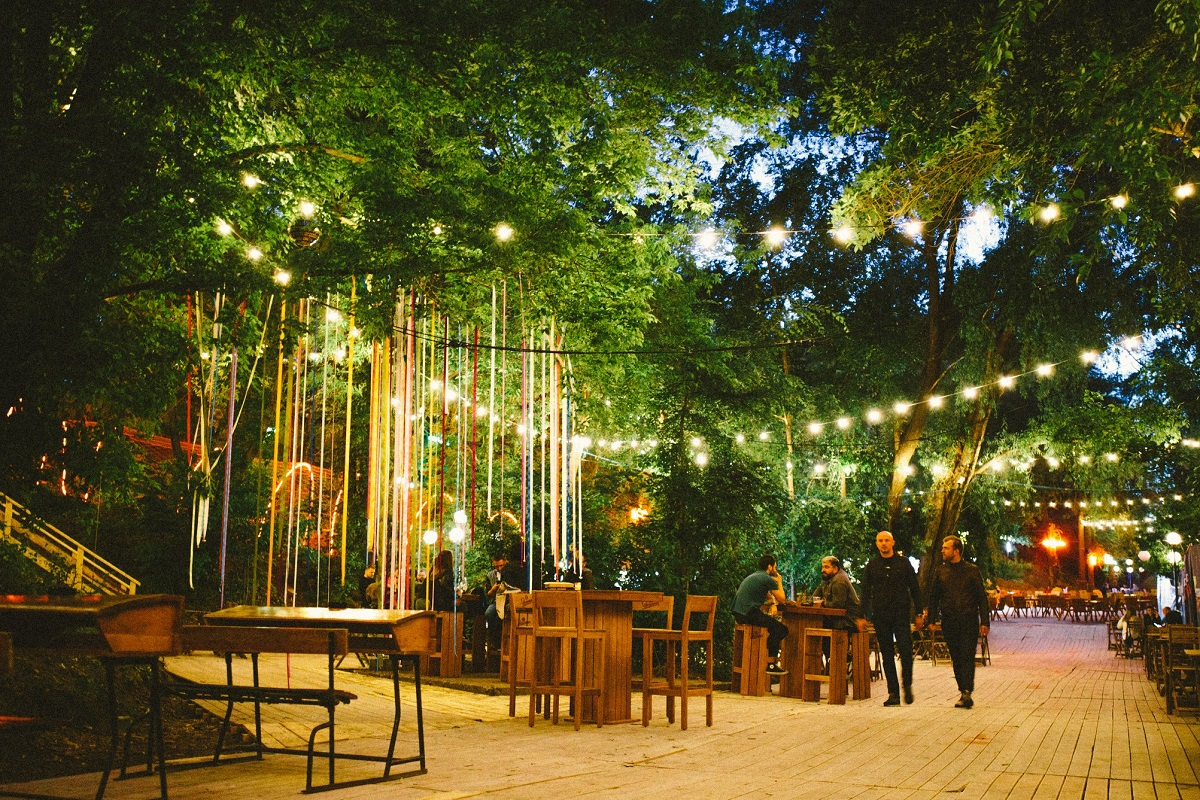 terasa popas nostalgia, cu mese asezate pe podea de lemn, lumini atarnate in copac si fasii colorate