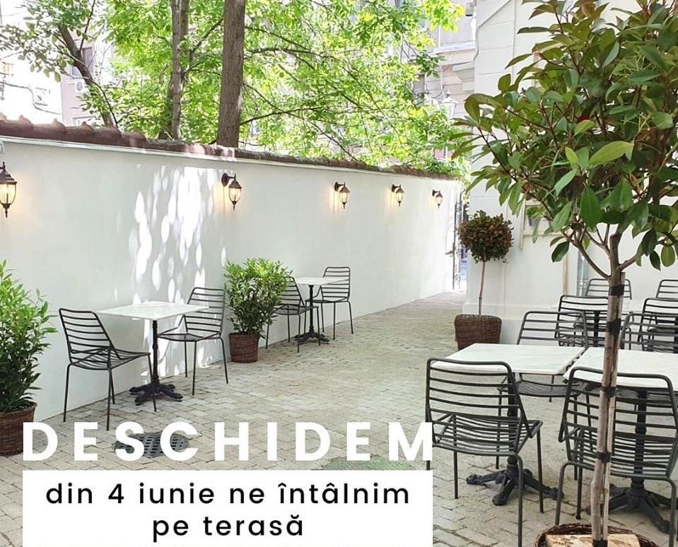 terasa de la NAika Restaurant, intr-o curte cu ziduri inalte, albe si mese cu cu saune din fier