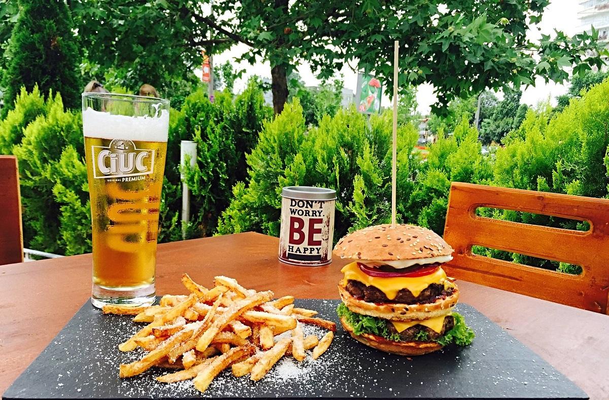 terasa zvetto burger bar, cu arbusti ornamentali si o masa de lemn cu un burger bun, cartofi prajiti si un pahar de bere