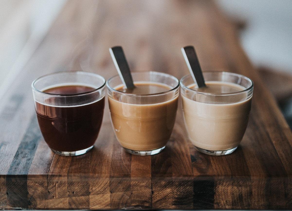 trei cești transparente cu cafea, una cafea neagra, alta capuccino si alta caffe latte