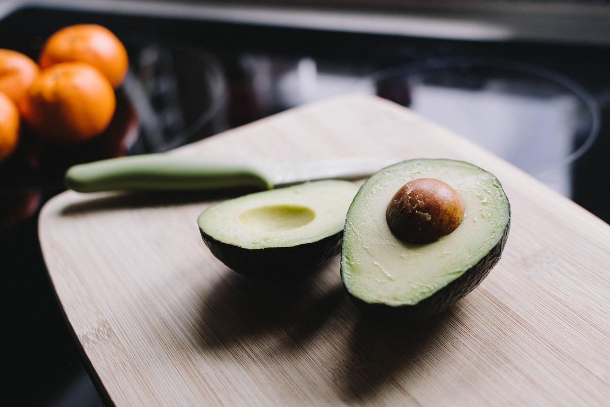 un avocado taiat pe jumatate, asezat pe un tocator de lemn, cu un cutit langa, ca ingrediente sănătoase la salată