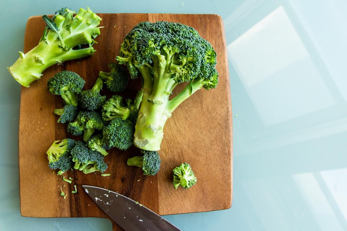 broccoli asezat pe un tocator, pe fundal albastru, ca ingrediente sănătoase la salată