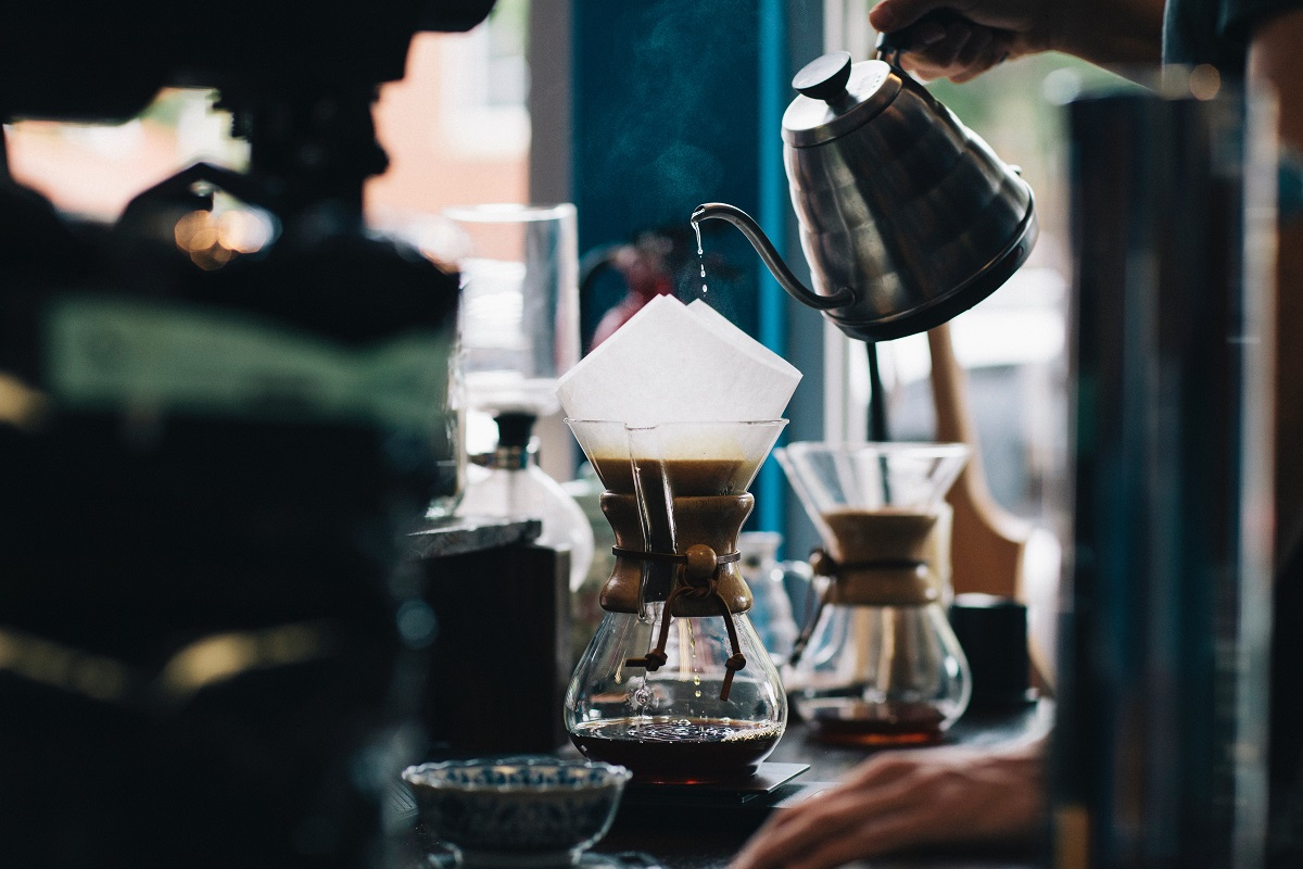 prim plan cu un ibric cu cafea care este turnata intr-o carafa de sticla, cu filtru de hartie