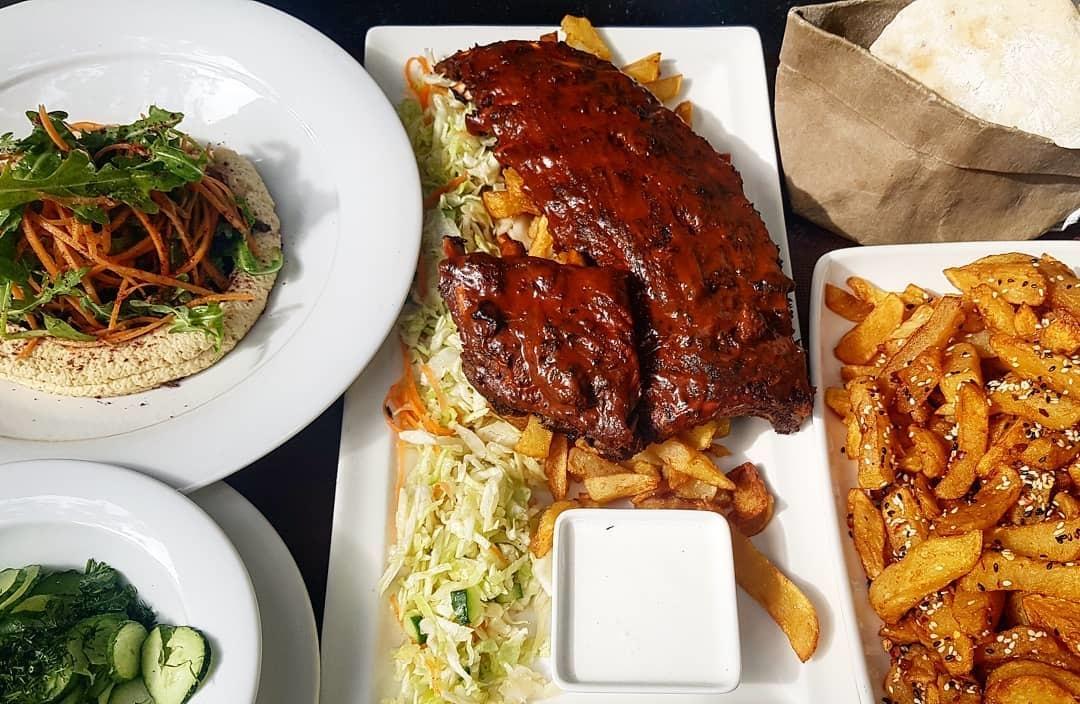 portie de coaste de porc, pe un platou cu cartofi prajiti si langa farfurie cu salata la restaurant energiea București