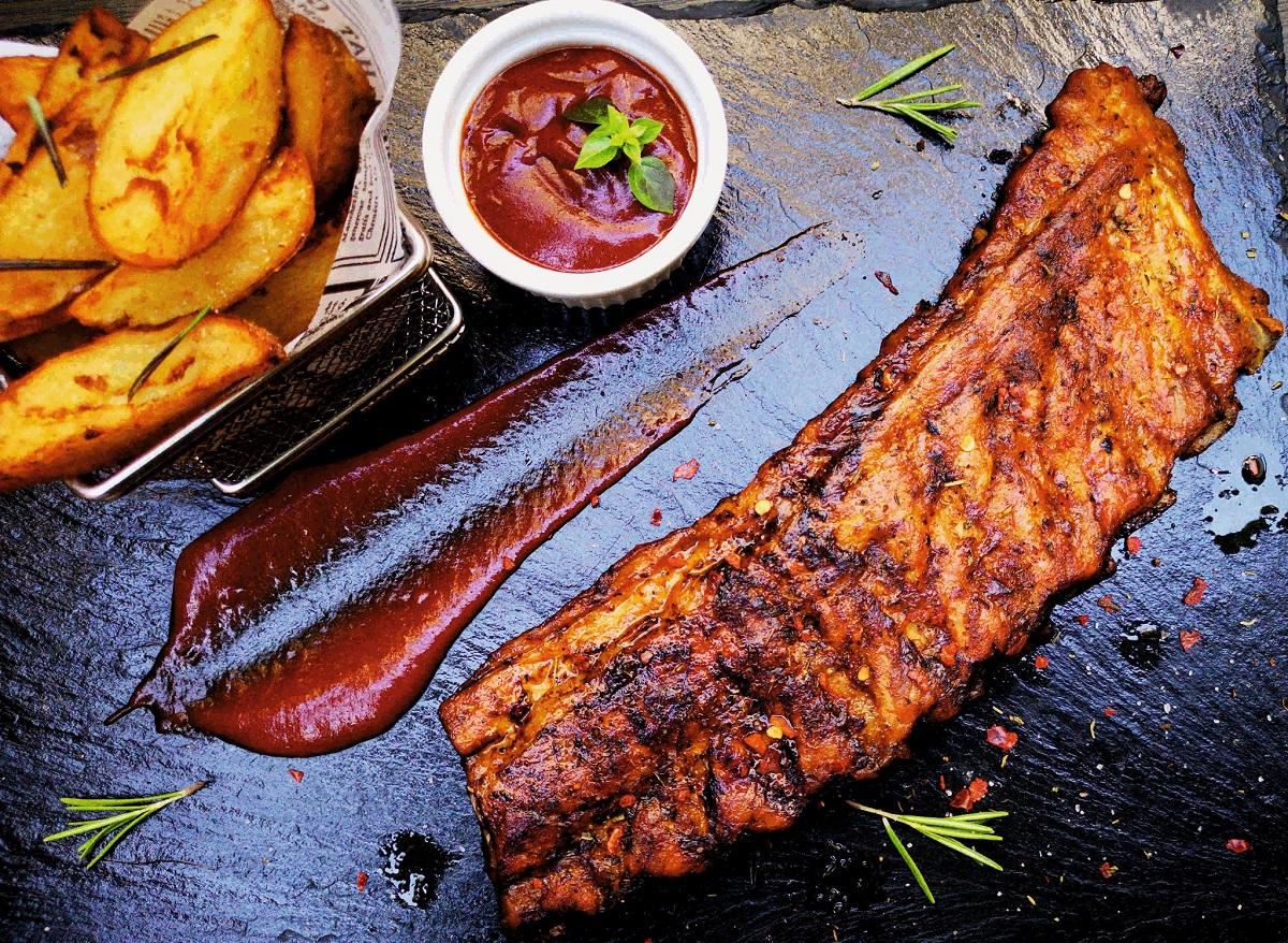 coaste de porc fotografiate pe fundal negru, cu un bol de ketchup langa si cartofi prajiti, la restaurant Journey Pub București