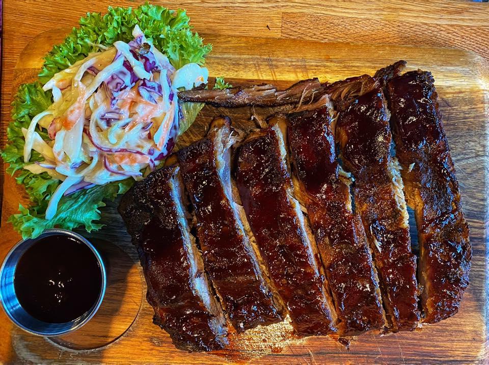 coaste de porc la restaurant Red Angus Steakhouse București, pe un platou de lemn, cu salata verde si sos